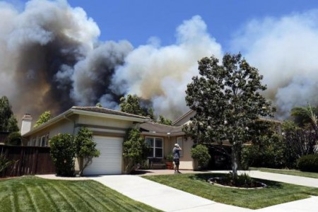 A man talks on a phone as a wildfire is seen approaching the neighborhood in Carlsbad, May 14, 2014.