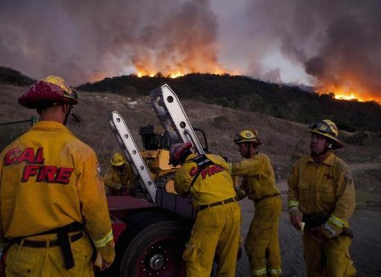 Firefighters battle a blaze in San Marcos, California May 14, 2014.