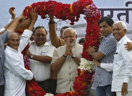 Hindu nationalist Narendra Modi, the prime ministerial candidate for India\'s main opposition BJP, gestures as he receives a garland from his supporters during a public meeting in Vadodara, in the western Indian state of Gujarat, May 16, 2014.